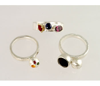 'Planet'- ring in silver set with fire opal, sapphire, ruby, chrome diopside and brown diamond 'Pyrope and Corundum' ring in Ecosilver and 18ct gold set with ruby, sapphire, and rhodolite garnet. 'Grounding' ring in silver set with a smoky quartz