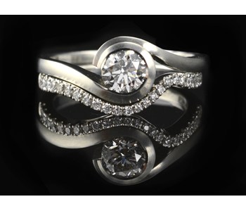 Platinum ring with a diamond partnered by platinum ring pavé set with diamonds